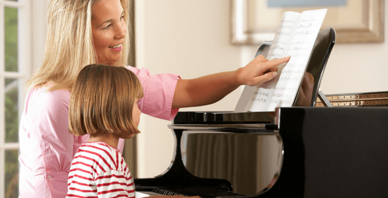 Music teacher teaching a child piano. Public Liability Insurance